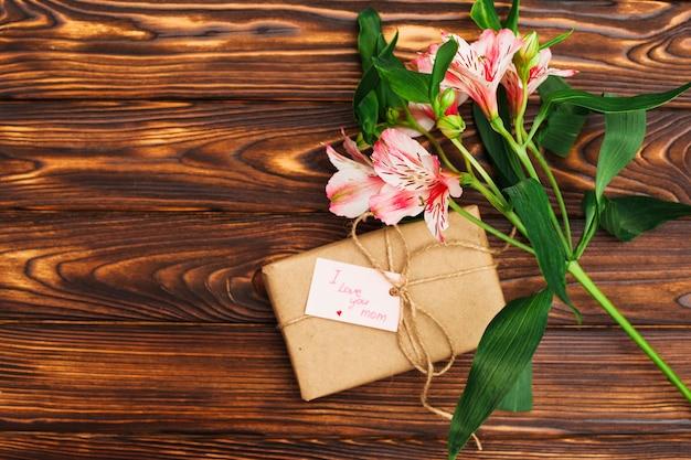 Te amo mamá inscripción con regalo y flores.