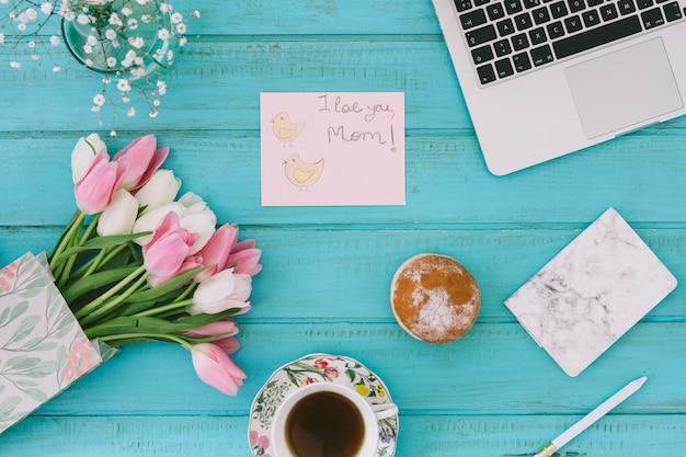 Te amo mamá inscripción con tulipanes y laptop.