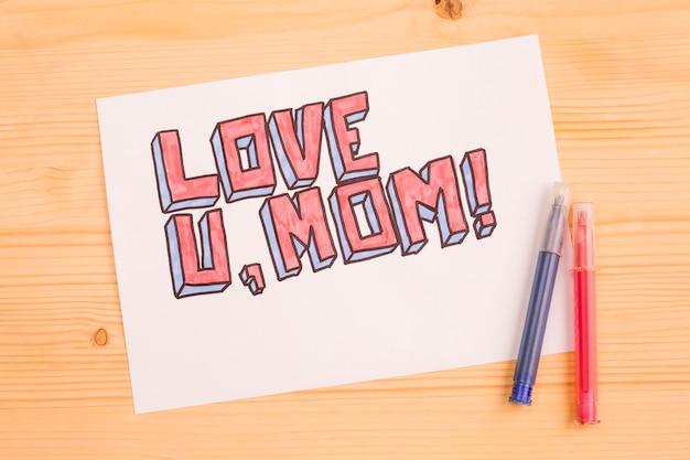 Te amo mamá tarjeta de papel sobre madera