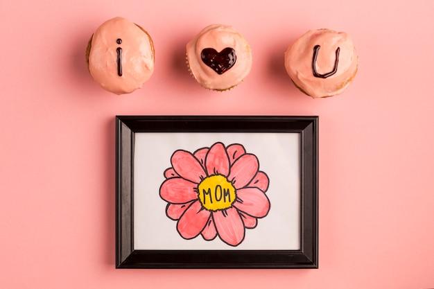 Te amo título en deliciosos cupcakes cerca del marco de fotos