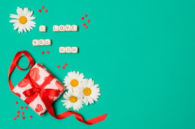 Te amo título de mamá cerca de flores blancas y caja de regalo.