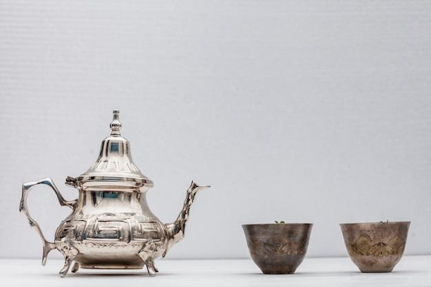 Té árabe en tazas con tetera en mesa blanca