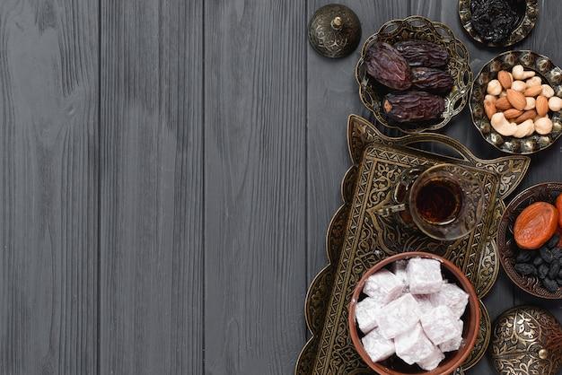 Té árabe tradicional de ramadán; lukum; frutos secos y nueces sobre tabla de madera
