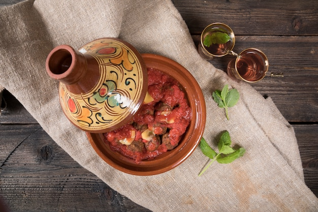 Té árabe en vasos con carne en tajine
