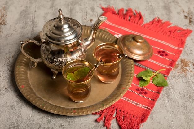 Té árabe en vasos con tetera sobre tela roja