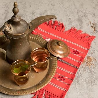Té árabe en vasos con tetera sobre tela