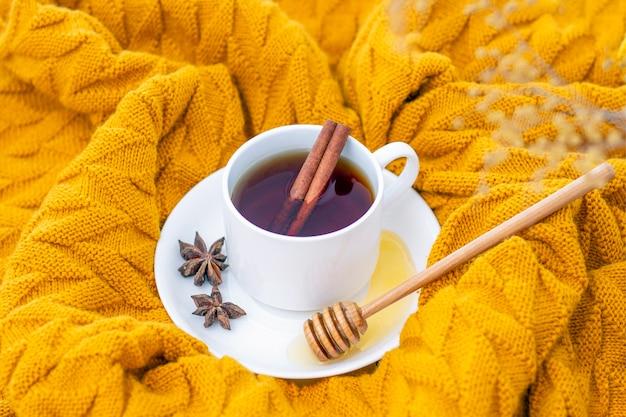 Té aromático de canela caliente cubierto con un cálido pañuelo sobre un fondo de madera de otoño. cazo de miel con miel