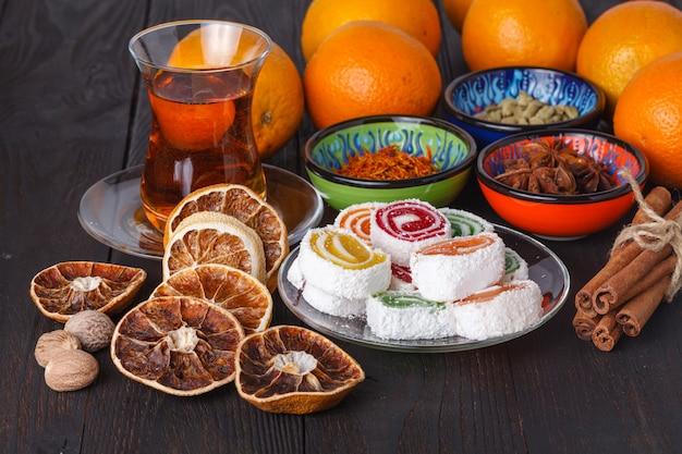 Té en azerbaiyán armudu tradicional y pila de dulces en la mesa