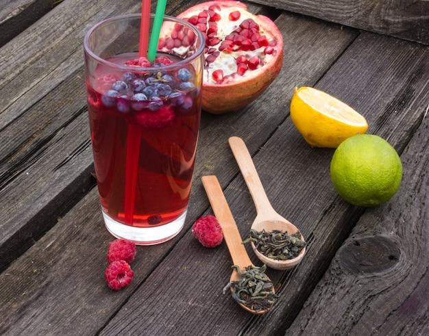 Té de bayas y frutas en vidrio sobre una mesa de madera. cosecha, otoño otoño invierno té caliente, bebida inmunidad.