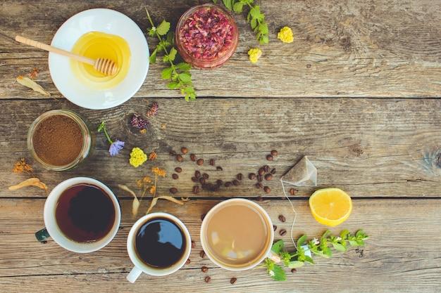Té, café, cacao en tazas, achicoria, limón, menta, mermelada de pétalos de rosa, limón seco, miel en la vista superior