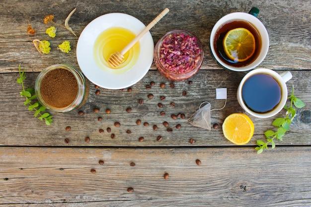 Té, café en tazas, achicoria, limón, menta, mermelada de pétalos de rosa, limón seco, miel sobre el fondo de madera viejo
