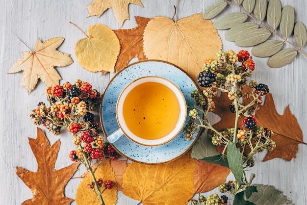 Té de calentamiento otoñal en una mesa de madera con hojas de árbol de otoño cerca