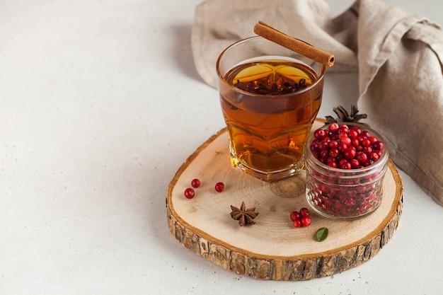 Té caliente con especias, bayas de manzana y arándano en una taza de vidrio transparente sobre un soporte de madera.