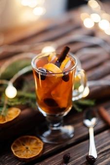 Té caliente y fruta de naranja en la mesa de madera