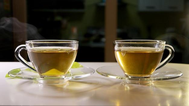Té caliente con humo en la taza de vidrio con platillos. concepto de alimentos y bebidas.