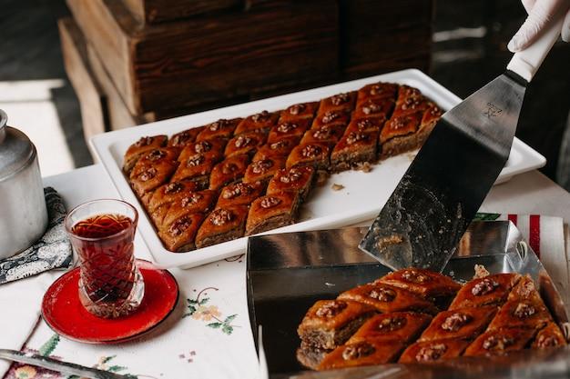 Té caliente junto con pakhlavas dulces en una mesa de tejido diseñada