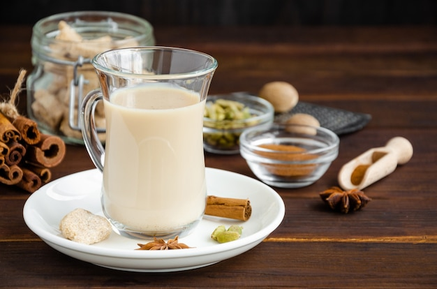 Té caliente con leche, canela, cardamomo, anís y otras especias, té indio masala en una taza de vidrio sobre un fondo de madera. copie el espacio.