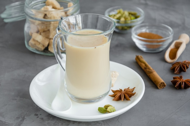 Té caliente con leche, canela, cardamomo, anís y otras especias, té indio masala en un vaso sobre un fondo oscuro.