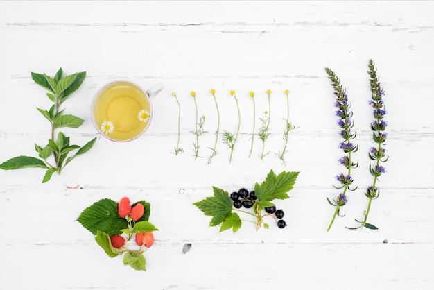 Té caliente sobre un fondo blanco de madera, los ingredientes para la preparación de té de hierbas natural