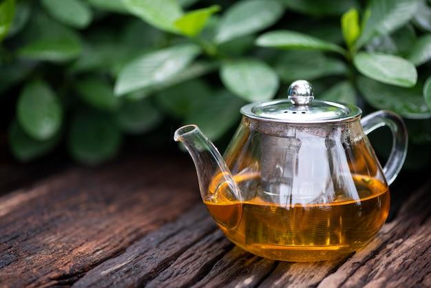 El té caliente con tetera de vidrio sobre la hoja de madera y verde