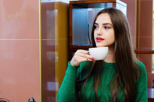 Té de consumición hermoso de la mujer joven en café