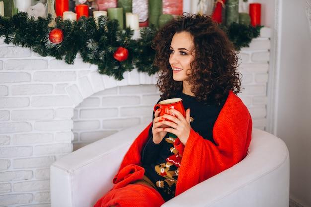 Té de consumición de la mujer joven por el árbol de navidad