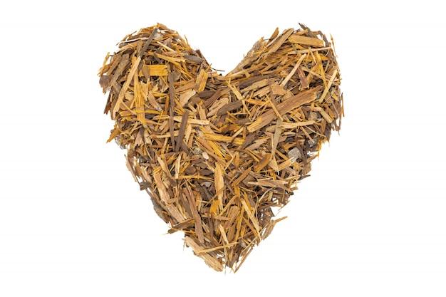Té de corteza de catuaba, aislado en forma de corazón. té de hierbas naturales de la corteza de árbol de catuaba en polvo.