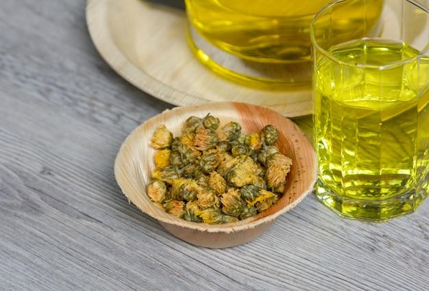 Té de crisantemo con té de crisantemo seco en un recipiente de madera sobre la mesa