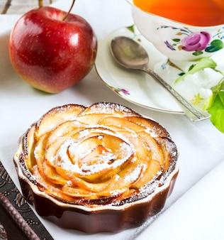 Té de desayuno con tarta de manzana dulce en forma de rosa