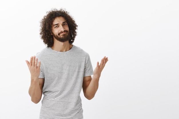 Te dije que tenía razón. hermoso modelo masculino oriental con barba y cabello rizado, levantando las manos y sonriendo, aliviado y diciendo finalmente