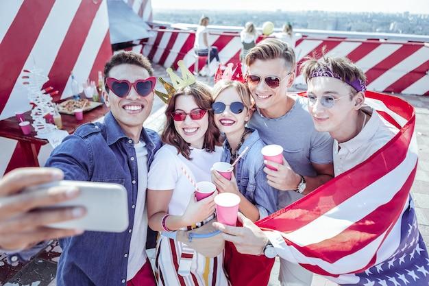 Te extrañaré. persona de sexo masculino joven que demuestra la bandera americana mientras celebra el día de la independencia