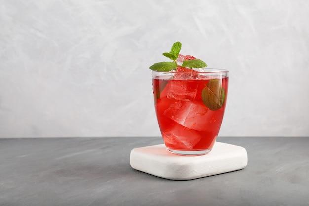 Té de frutas helado en vidrio transparente sobre posavasos blancos sobre fondo blanco y gris