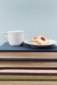 Té y galletas en la pila de libros