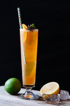 El té helado de durazno negro consiste en jarabe de vainilla, especias y jugo de limón en un primer plano de vidrio sobre una mesa de madera sobre fondo oscuro