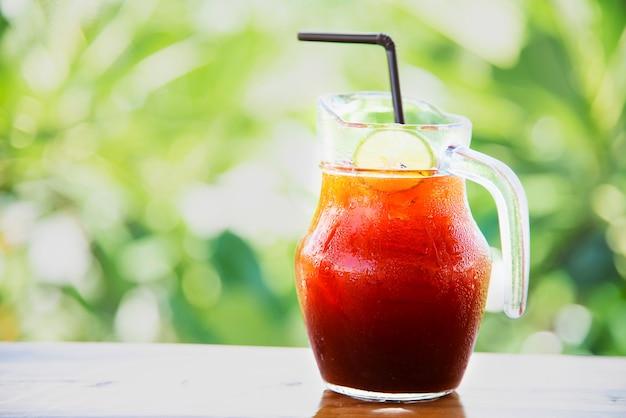 Té helado en la mesa de madera sobre jardín verde - relájese con una bebida en concepto de naturaleza