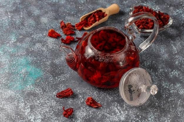 Té de hibisco caliente en una taza de vidrio y una tetera de vidrio.