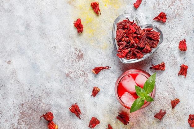 Té de hibisco frío con hielo y hojas de albahaca.