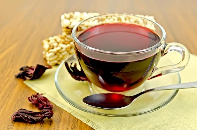 Té de hibisco en una taza de vidrio, té de pétalos secos, pan crujiente de cereales en una servilleta amarilla y una tabla de madera