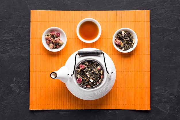 Té de hierbas aromáticas e ingrediente con tetera de cerámica blanca sobre mantel naranja