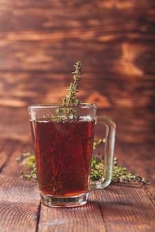 Té de hierbas aromáticas con racimos de tomillo en una taza de vidrio