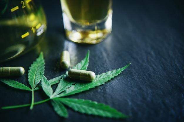 Té de hierbas y cápsulas de cannabis con planta de hoja de marihuana sobre fondo oscuro