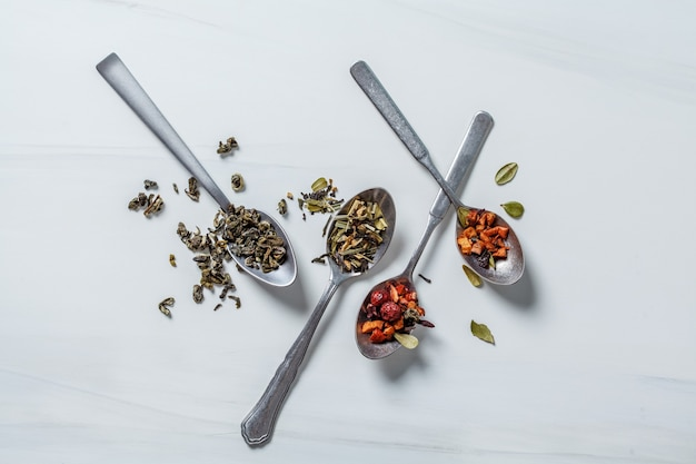 Té de hierbas diferentes con miel y especias sobre un fondo blanco.