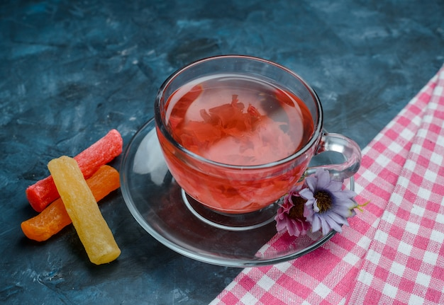 Té de hierbas con dulces, flores en una taza en azul y paño de cocina, vista de ángulo alto.