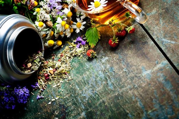 Té de hierbas con flores en la mesa de madera