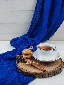 Té de hierbas, galletas y panqueques sobre tabla de madera