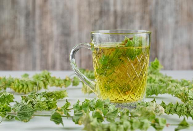 Té de hierbas con hojas en un vaso de vidrio blanco y sucio,
