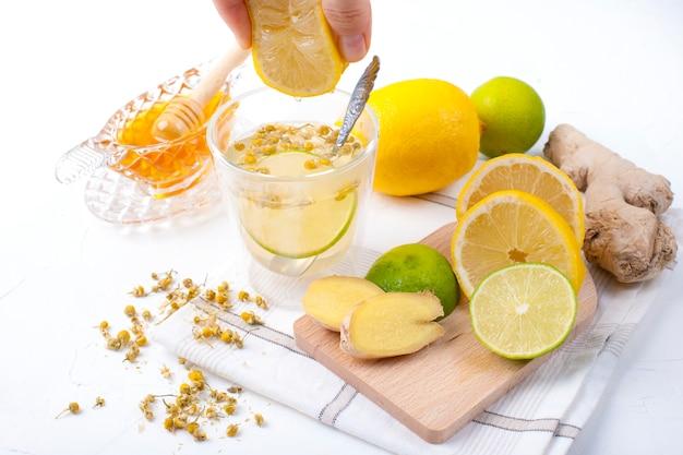 Té con hierbas, limón y jengibre sobre fondo blanco y miel