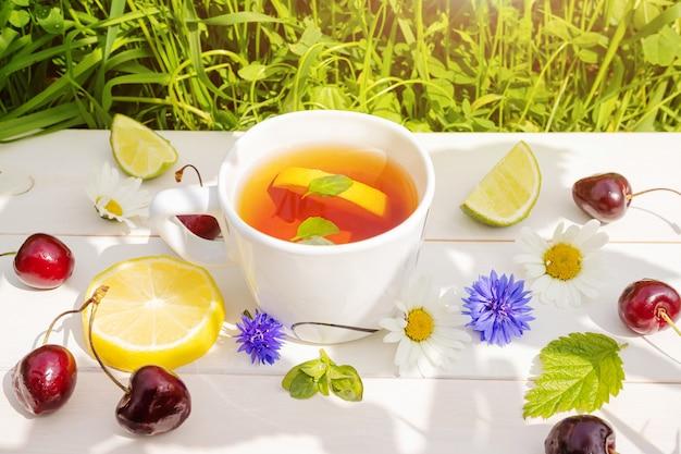 Té de hierbas con limón y menta en bandeja de madera blanca sobre fondo de hierba.