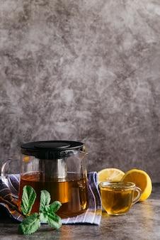 Té de hierbas de limón y menta en vaso de vidrio transparente y tetera