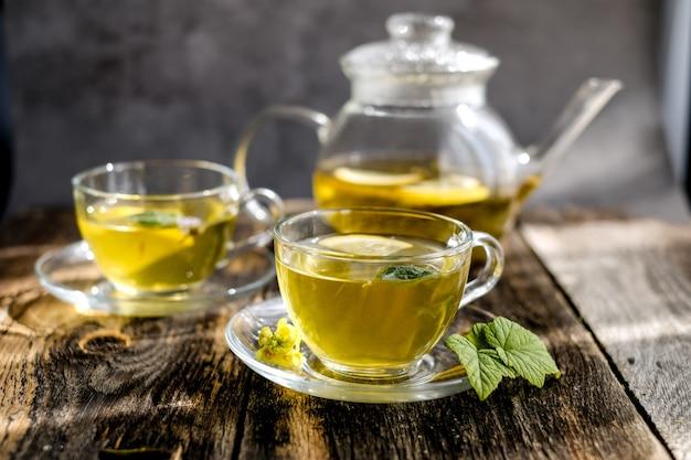Té de hierbas con limón y miel en vaso de vidrio y tetera